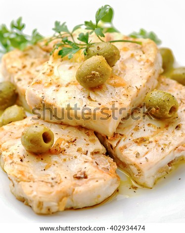 Cod fillet with green olives parsley, olive oil on white background