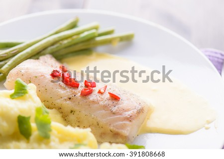 Cod fillet with mashed potatoes topped with some chili - stock photo