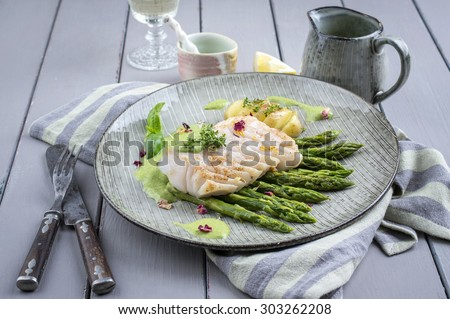 cod fish fillet with green asparagus - stock photo