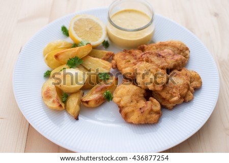 Cod fish in batter or cod fritters served with baked potatoes with parsley leaves and home made mayonnaise sauce and half of lemon served on the simple white plate. Light dish for lunch or diner.