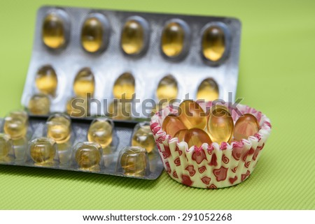 Cod liver fish oil omega 3 gel capsules isolated on green background. Golden yellow vitamin capsules in metal foil blister strip packaging. A nutritional supplement contains vitamin A and vitamin D, - stock photo