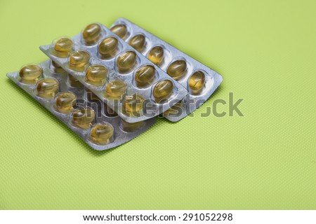 Cod liver fish oil omega 3 gel capsules isolated on green background.  Golden yellow vitamin capsules in metal foil blister strip packaging. A nutritional supplement contains vitamin A and vitamin D. - stock photo