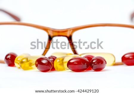 Cod liver oil omega 3 gel capsules  and eyeglasses - stock photo