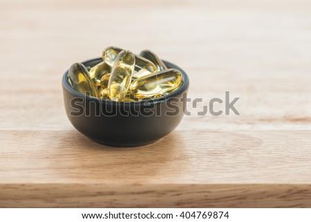 Cod liver oil omega 3 gel capsules in bowl on floor wood - stock photo
