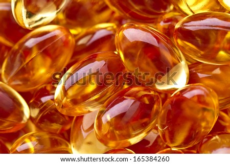 Cod liver oil omega 3 gel capsules isolated on pastel background. Vitamin d pils. Pils in Hearth shape bowl - stock photo