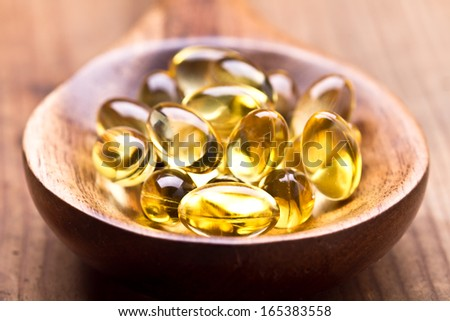 Cod liver oil omega 3 gel capsules isolated on wooden background  - stock photo
