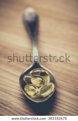 Cod liver oil omega 3 gel capsules isolated on wooden background. Vitamin D capsuls. dietary supplement - stock photo