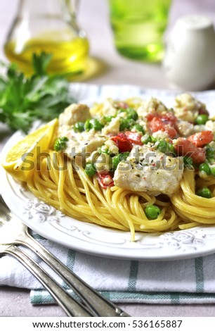 Codfish in a cream sauce with vegetables garnished with spaghetti on a concrete,stone or slate background.