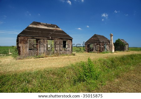 Codigoro (Fe),Emilia Romagna,Italy, traditional old buildings of wood and straw for farm on the edge of a field of tomatoes