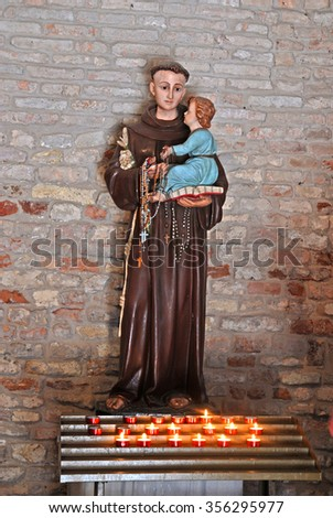 CODIGORO, ITALY-MAY 10, 2015: Pomposa Abbey Saint Mary church interior monk with baby Jesus statue. The place attract thousands of people every year.
