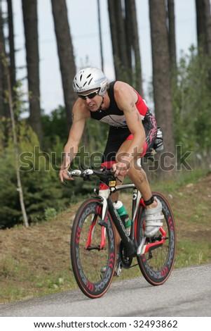 COEUR D'ALENE, IDAHO, JUNE 21: Triathlete Balazs Csok of Hungary on the bike portion of the Coeur d'Alene Ironman Triathlon in northern Idaho on June 21, 2009, - stock photo