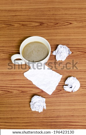 coffe cup and crumpled for idea on wood background
