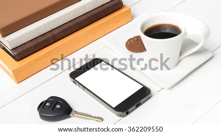 coffe cup with cookie,phone,car key and stack of book on white wood table