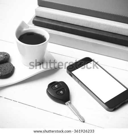coffe cup with cookie,phone,car key and stack of book on white wood table black and white color