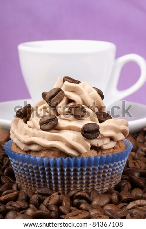 Coffe cupcake and a cup of espresso among coffee beans over a pink background - stock photo