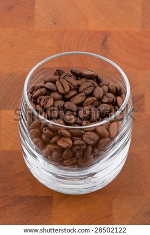 coffea beans in glass on wooden table - stock photo