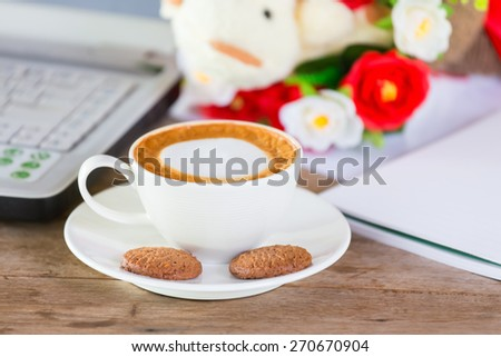 Coffee and a cookie is placed on a desk. - stock photo