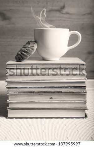 Coffee and a cookie on top of books