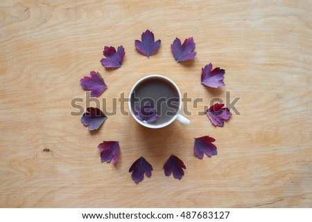 Coffee and autumn leaves on wooden background