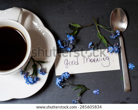 Coffee and blue flowers (forget-me-nots) on a stone and wooden background with good morning note