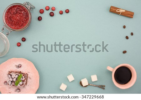 Coffee and chocolate cake with cranberry jam and cinnamon on wooden board, over turquoise background. Top view, copy space. - stock photo