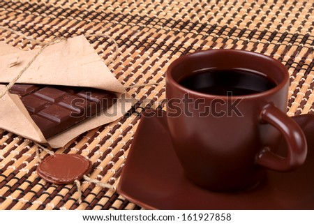 Coffee and chocolate in a box with a wax seal on a background of a bamboo napkin
