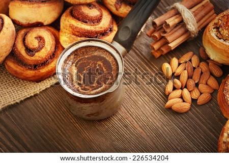 coffee and cinnamon rolls on wooden blackboard - stock photo