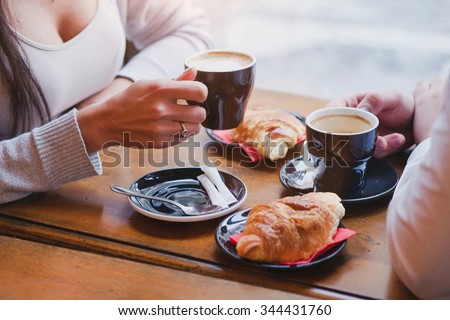 coffee and croissants in cafe, hands of couple closeup - stock photo