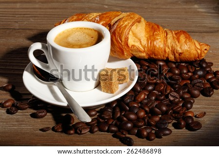 Coffee and croissants on wooden table shallow dof - stock photo