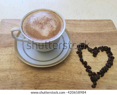 Coffee and heart. Coffee beans makes coffee Heart. Coffee & beans on wooden table, coffee cup & coffee beans background, coffee background with beans, colorful design coffee & coffee beans, coffee art - stock photo