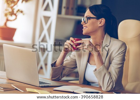 Coffee and ideas. Cheerful young beautiful businesswoman in glasses holding coffee cup and looking away with smile while sitting at her working place - stock photo