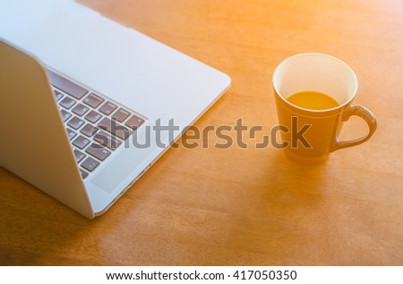 coffee and laptop with Sun light,Soft focus - stock photo