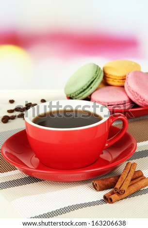 Coffee and macaroons on table on light background