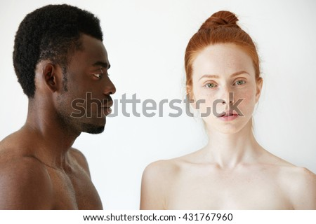Coffee and milk. Portrait of young multi-ethnic couple posing naked against white studio wall. Profile of African man looking at his Caucasian girlfriend with love and affection. Interracial relations - stock photo