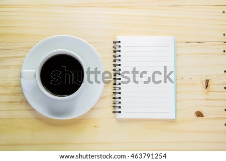 Coffee and notepad on wood table