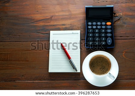 Coffee and red pen on notes and calculator with nature wood background,copy space