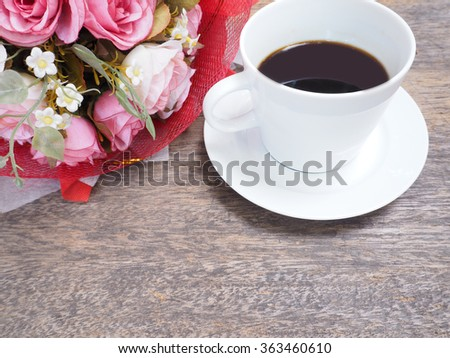 coffee and rose flower on wooden table - stock photo