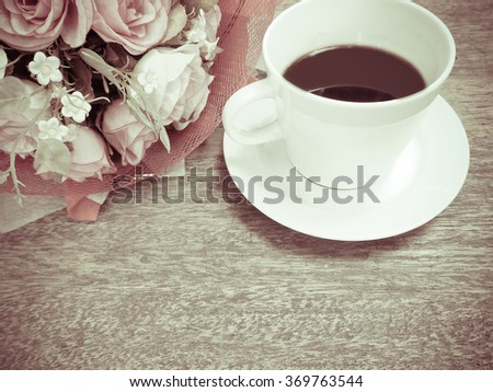 coffee and rose flower on wooden table, vintage filter effect - stock photo