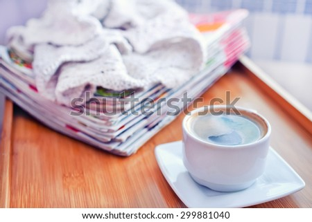 coffee and stack of magazins on wooden tray - stock photo