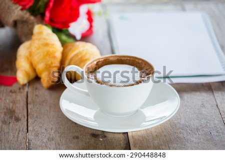 Coffee and sweets laid on a wooden table. - stock photo