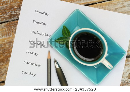 Coffee and weekdays listed on white piece of paper  - stock photo