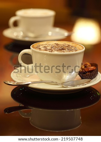 Coffee art: two cups of coffee latte  on dark background - stock photo