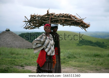 COFFEE BAY, SOUTH AFRICA, JANUARY 13, 2007: Two unidentified African women resting while carrying wood for the fire with the nature and a hut in the background. Garden Road, South Africa 2007 - stock photo