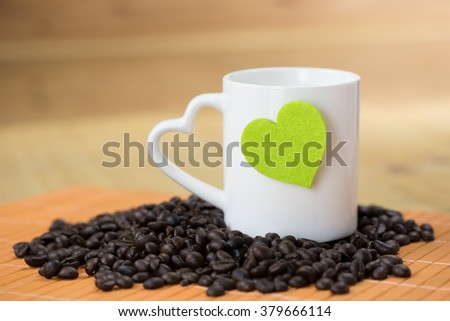 Coffee bean and green heart shape with white mug which has heart handle