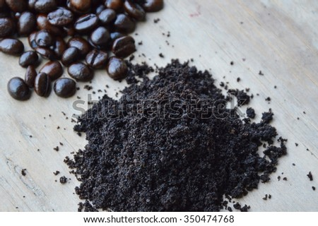 coffee bean and powder on wooden board - stock photo