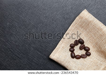 Coffee bean arrange to the shape of heart put on the coffee bean sack in the scene appear the back color leather background - stock photo