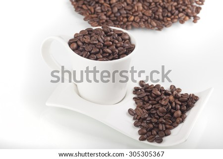 Coffee bean in coffee cup isolated on white