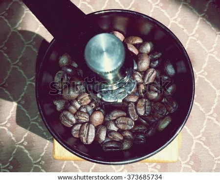 Coffee bean  in manual coffee grinder in view from the top - stock photo