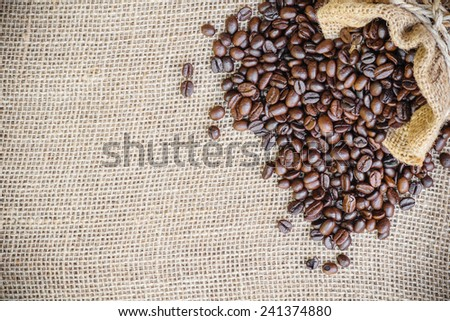 coffee bean in sack bag on burlap background - stock photo