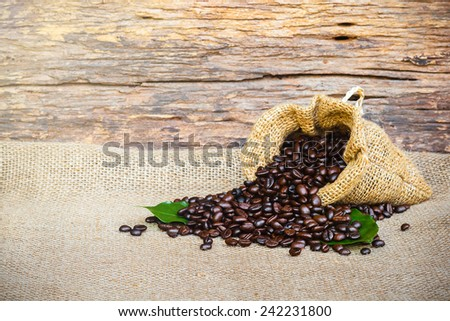 coffee bean in sack bag on burlap old wood background - stock photo